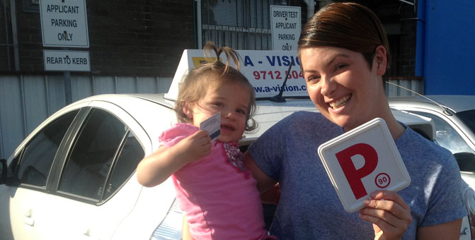 Young woman and child holding P plates